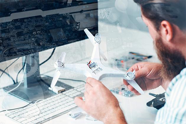 Homem mexe nas peças que compõem o drone branco