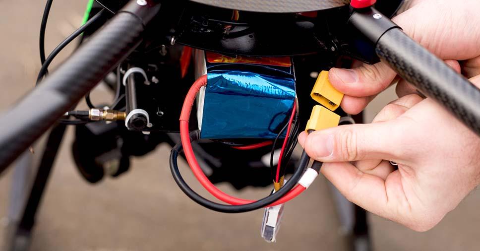 Na imagem vemos um piloto melhorando a bateria do drone. Saiba como também no artigo!